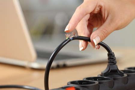 Schließen Sie oben von einer Frauenhand, die ein gefährliches beschädigtes elektrisches Kabel hält Standard-Bild