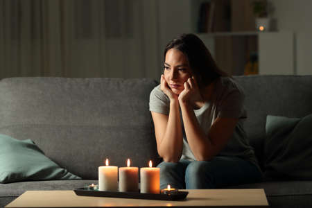 Frustrated woman sitting at home during a blackout sitting on a couch in the living room at home Stok Fotoğraf