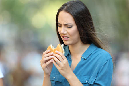 Disgusted woman eating a burger with bad taste on the street
