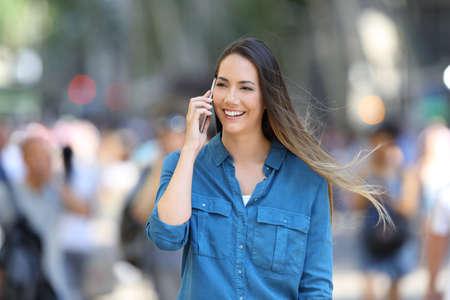 Mujer feliz en azul habla por teléfono caminando en la calle Foto de archivo