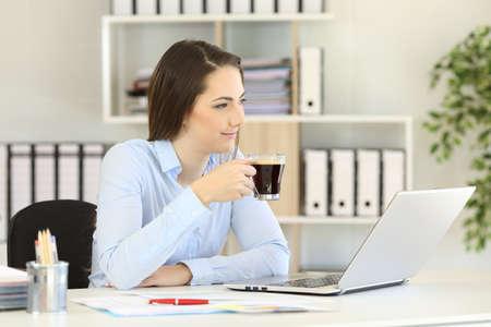 Office worker relaxing looking away during a coffee break