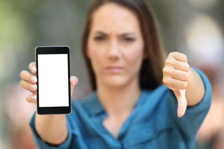 Front view portrait of a negative woman showing a blank smart phone screen on the street
