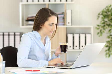 Büroangestellter, der online mit einem Laptop arbeitet, der eine Kaffeetasse hält