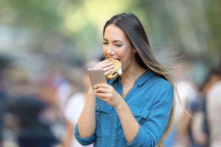 Happy woman eating a burger holding a smart phone on the street