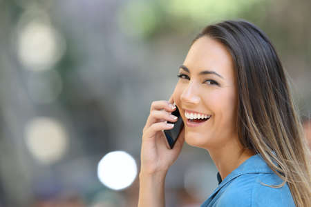 Happy girl talks on phone smiling in the street looking at camera