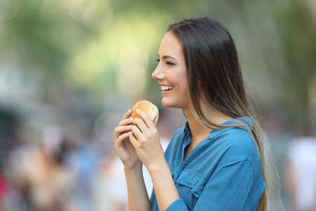 Profile of a woman holding a burger on the street