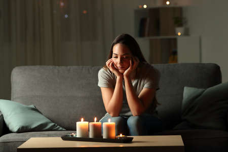 Distracted woman looking at candles light during blackout sitting on a couch in the living room at home Фото со стока