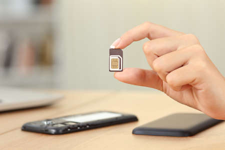 Close up of a woman hand holding sim card different sizes at home