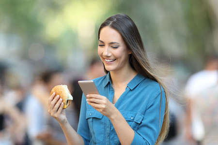 Woman holding a burger checking smart phone on the street