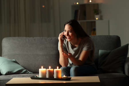 Happy woman talking on phone in the night sitting on a couch in the living room at home