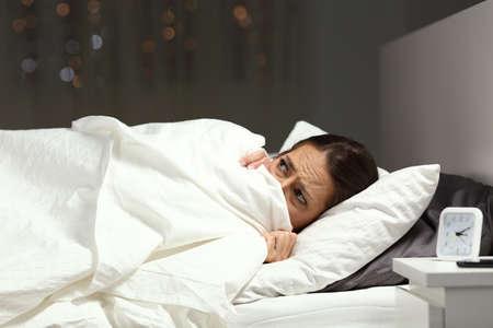 Mujer asustada escondida debajo de una manta acostada en una cama en la noche en casa