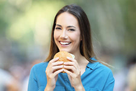 Front view portrait of a woman holding a burger looking at camera