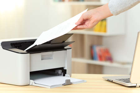 Schließen Sie oben von einer Frauenhand, die ein Dokument von einem Drucker auf einem Schreibtisch zu Hause fängt Standard-Bild