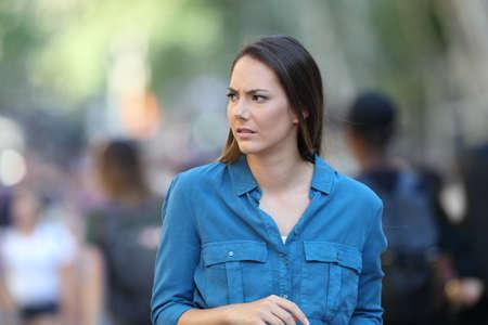 Ängstliche Frau, die auf der Straße geht, die Seite schaut