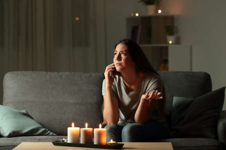 Lady claiming electric company for a blackout sitting on a couch in the living room at home
