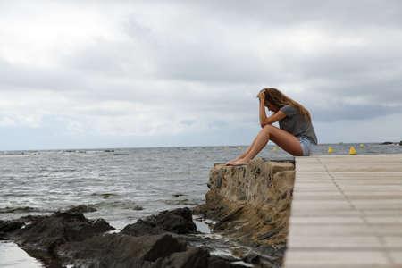 Portrait de profil complet du corps d'une jeune fille déprimée se plaignant assis sur la plage