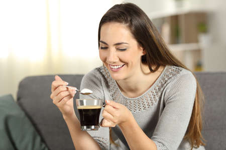 Girl holding a spoon with sugar and a coffee cup sitting on a couch in the living room at home