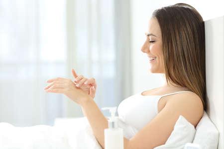 Retrato de vista lateral de una mujer feliz aplicando crema humectante en las manos en una cama