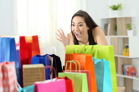 Amazed woman looking at multiple colorful shopping bags at home