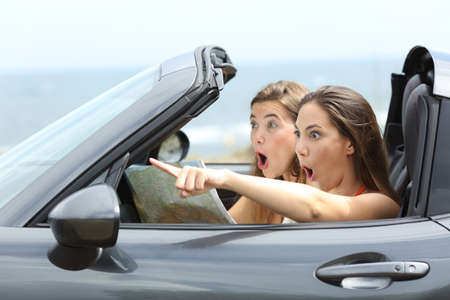 Amazed girls in a car pointing away on summer vacations 스톡 콘텐츠 - 105199286