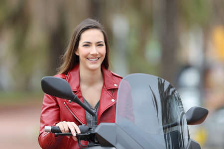 Happy biker posing looking at camera sitting on her motorbike on the street Stock Photo - 105199289