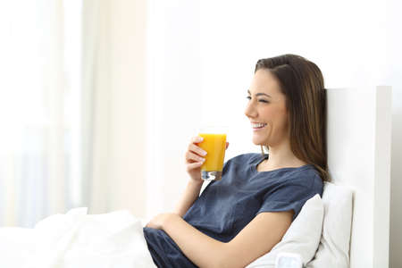 Happy woman lying on a bed holding an orange juice for breakfast at home Stock Photo