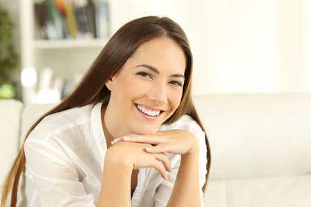 Housewife looking at camera with perfect smile sitting on a couch in the living room at home Stock Photo