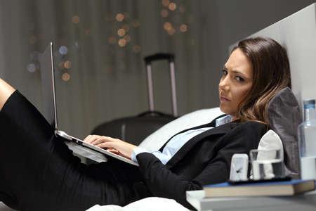 Unglücklicher Arbeiter, der online arbeitet und spät in der Nacht in einem Hotelzimmer in die Kamera schaut