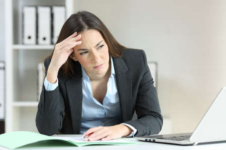 Front view portrait of a worried office worker looking at side