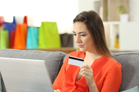 Lady paying online with a credit card and a laptop sitting on a couch in the living room at home