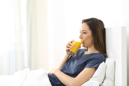 Woman drinking orange juice for breakfast lying on a bed in the morning at home