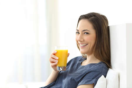 Happy woman looking at camera holding an orange juice for breakfast