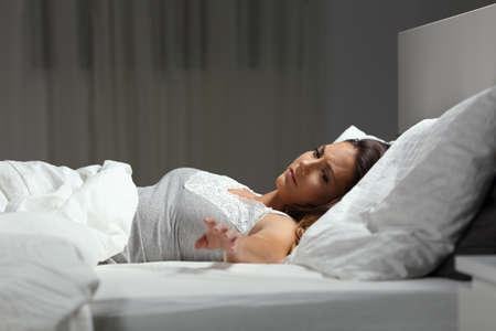 Sad single woman missing her husband in the night on a bed at home Stock Photo