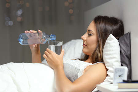 Profile of a woman drinking water on a bed in the night at home