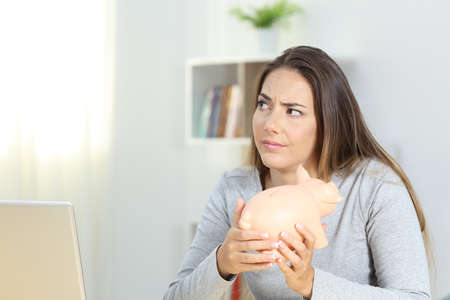 Confused woman holding a piggy bank at home