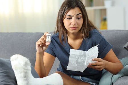 Confused disabled girl reading a leaflet of painkiller pills sitting on a couch in the living room at home