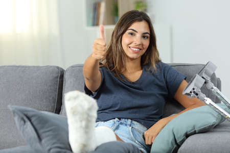Happy disabled woman with thumbs up sitting on a couch in the living room at home Stock Photo
