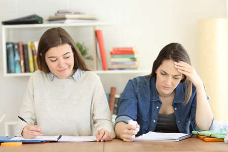 Resentful student happy to see her frustrated friend failing Stock Photo