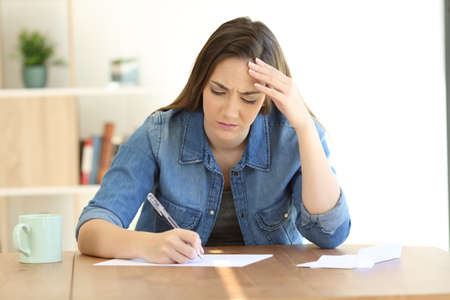 Worried woman writing a letter on a table at home Stock Photo