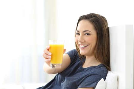 Mujer feliz sentado en la cama que muestra un vaso de jugo de naranja en casa Foto de archivo - 107055437