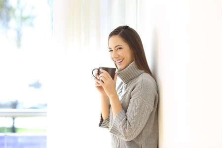 Niña feliz mirando la cámara que sostiene una taza de café de pie en casa en invierno Foto de archivo - 107031539