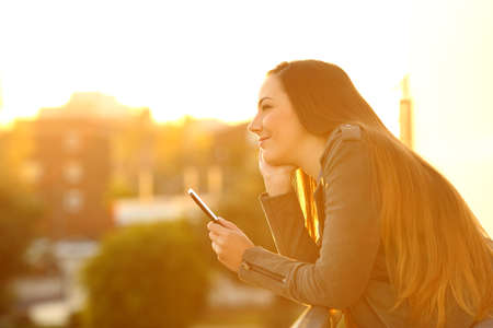 Side view portrait of a pensive girl holding a phone at sunset in a house balcony