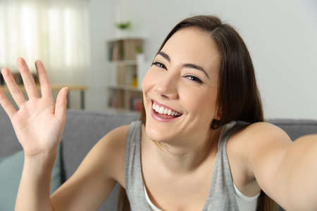 Portrait of a girl waving recording video or taking selfie at home