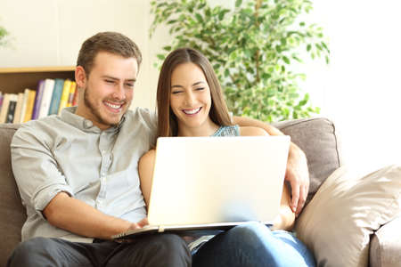 Happy couple using a laptop sitting on a couch in the living room at home Banque d'images - 107055447