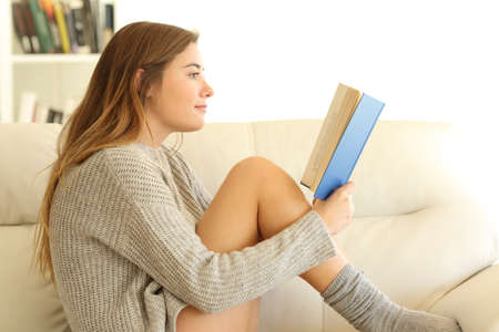 Profile of a teen reading a book sitting on a couch in the living room at home