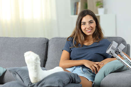 Happy disabled woman posing looking at camera sitting on a couch in the living room at home