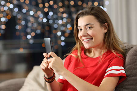 Teen looking at you holding a phone in the night sitting on a couch in the living room at home Stock Photo