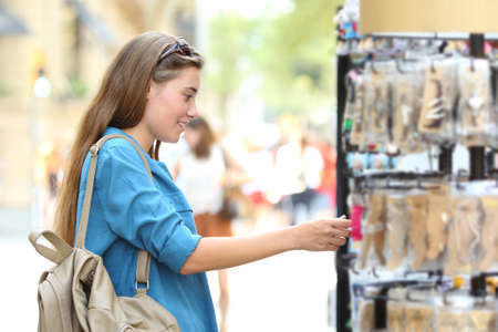 Side view portrait of a happy woman searching products in a showcase in the street Stock Photo