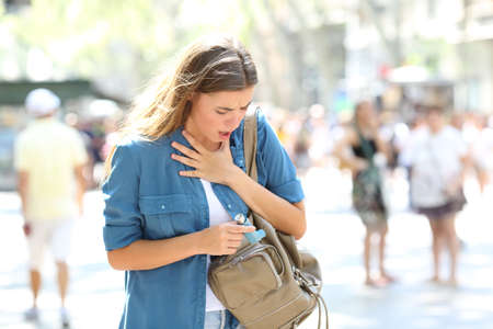 Asthmatic girl suffering an attack and searching the inhaler in a bag in the street