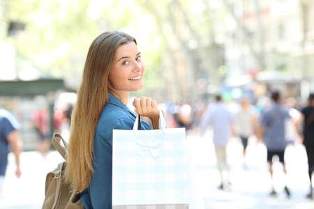 Beauty shopper showing blank shopping bags walking in the street